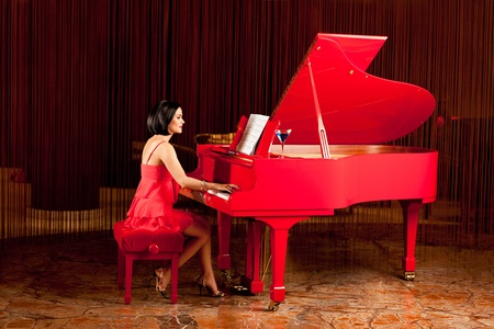 elegant brunette woman in red dress playing piano photo