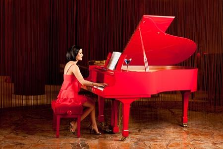 tocando el piano: mujer Morena elegante vestido rojo tocando el piano