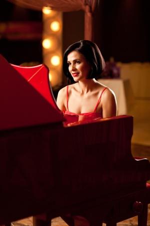 pianista: mujer hermosa morena en el piano rojo jugando a disfrazarse Foto de archivo