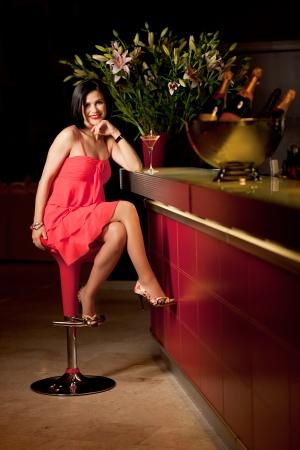 mujeres sentadas: vestido de rojo hermosa mujer barra sonrisa de contador