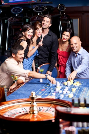 young, happy people playing the casino roulette  photo