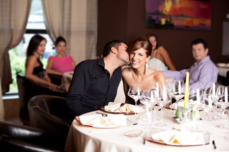date night: romantic young couple in restaurant date kiss