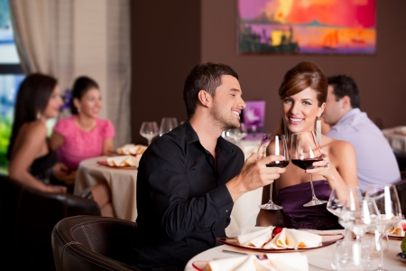 romantic kiss: romantic young couple at restaurant table toasting