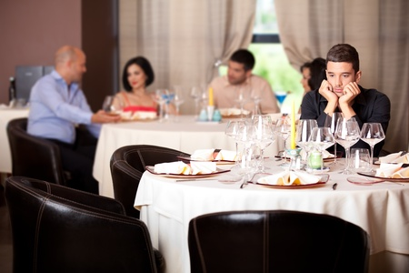 lonely man: sad young man waiting date restaurant table