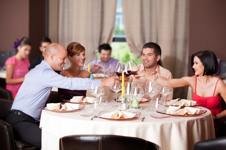 dinner party people: happy young couples toasting restaurant table