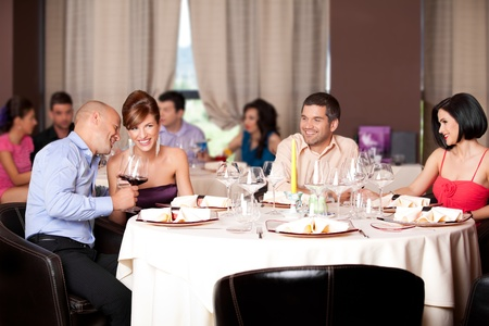 party dress: happy young couples talking restaurant table  Stock Photo