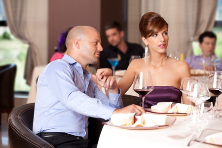 man flirting, woman distracted at restaurant table photo