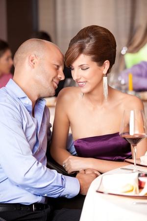 date night: happy couple flirting at restaurant table Stock Photo