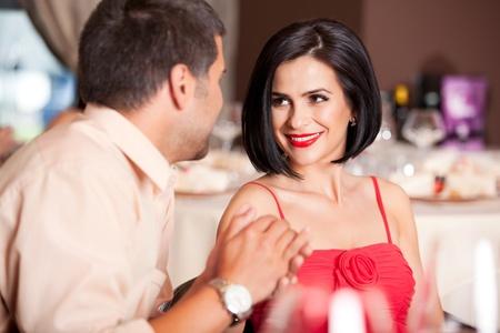 dinner date: happy couple flirting at restaurant table Stock Photo