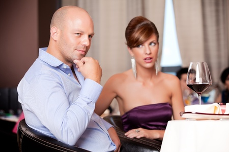 man thinking, woman suspicious at restaurant table photo