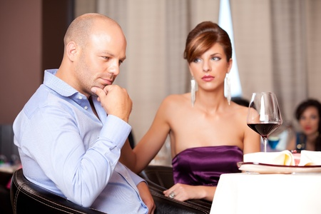 man thinking, sad woman at restaurant table photo