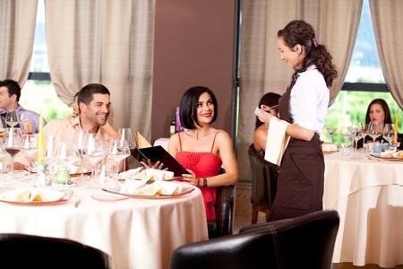 camarero: camarera teniendo pareja joven cena orden restaurante tabla Foto de archivo