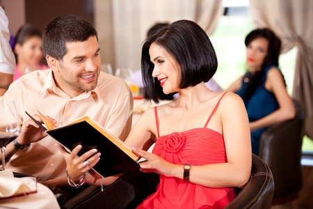 young couple deciding menu order restaurant table  photo