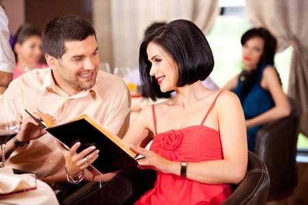 serving food: young couple deciding menu order restaurant table