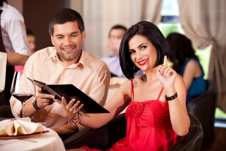 couple dining: young couple calling waiter restaurant table Stock Photo
