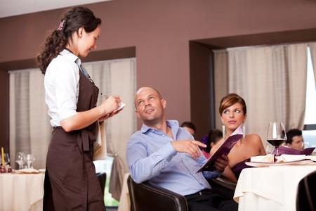 meseros: camarera teniendo pareja joven cena orden restaurante tabla Foto de archivo