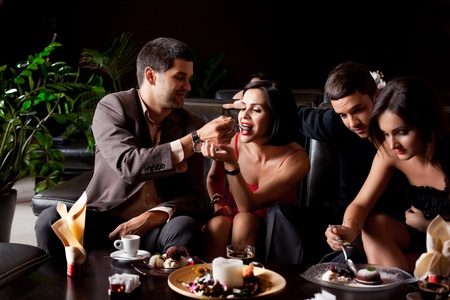 party food: happy young couples eating deserts coffee