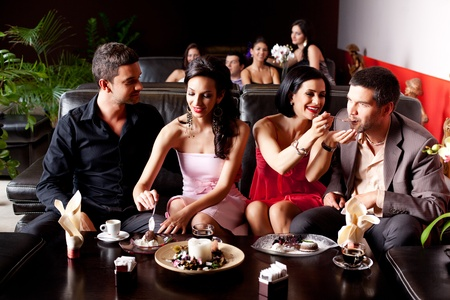 dinner date: young couples eating deserts feeding each other  Stock Photo