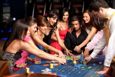 roulette table: caucasian smiling adults and croupier placing bets