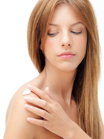 blonde woman applying body lotion on shoulder photo