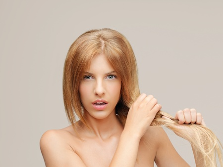 young woman pulling damaged hair both hands photo