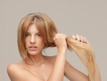 ambos: mujer joven tirando el pelo da�ado las dos manos