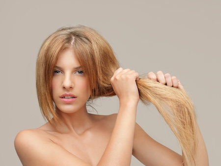 young woman pulling damaged hair both hands Stock Photo - 10914150