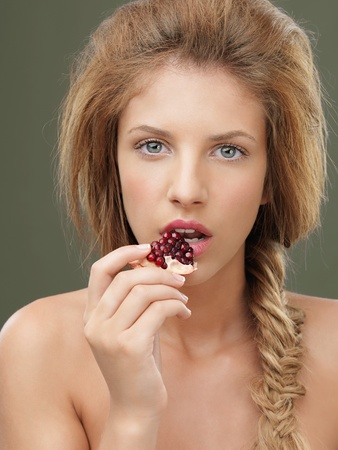 beautiful young blonde woman tasting a pomegranate