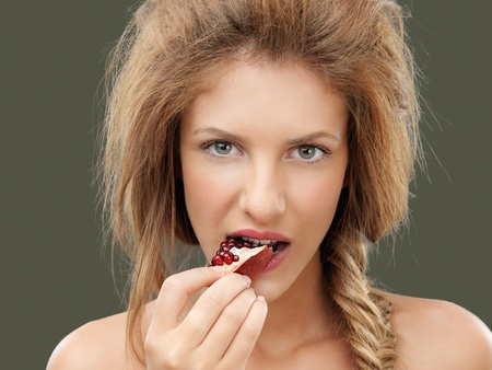 beautiful young blonde woman biting a pomegranate Stock Photo