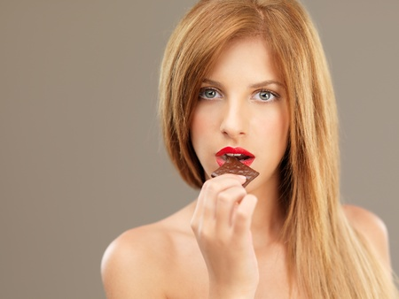 open lips: sexy blonde woman red lips eating chocolate
