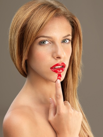 beauty portrait sexy woman smudging red lipstick photo