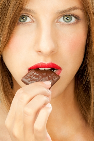 woman with red lips bitting chocolate bar Stock Photo - 10918544