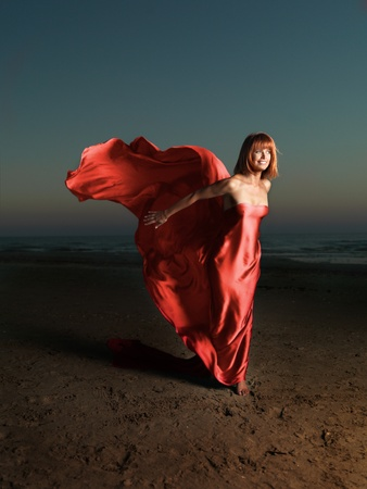 young woman beach red silk wind blowing photo