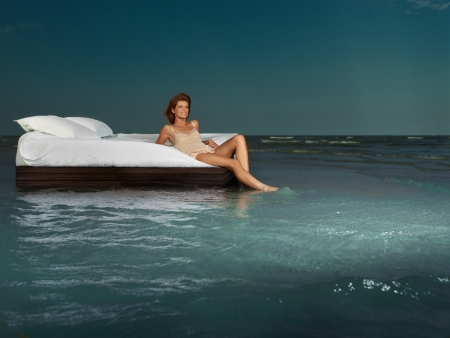 white pillow: young woman laying bed surrounded by sea Stock Photo