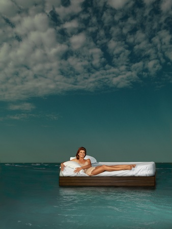 sea bed: young woman laying bed surrounded by sea Stock Photo