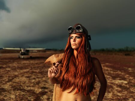 fashion portrait woman aviator outfit smokey sky photo