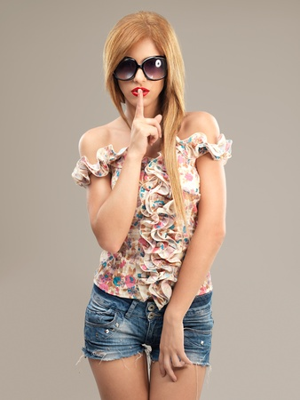 sexy blonde woman with sunglasses and jeans shorts posing at camera