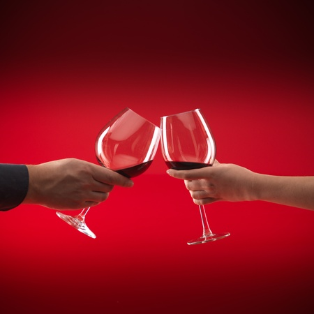 hands of man and woman holding glasses of red wine, toasting, on red background Stock Photo - 10963956