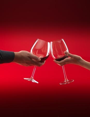 manos de hombre y mujer con vasos de vino tinto, tostado, sobre fondo rojo