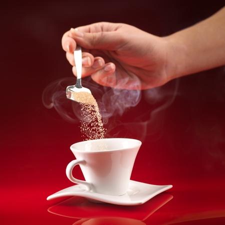 personas tomando cafe: mano de la mujer vertiendo panela en blanco taza de caf� sobre fondo rojo Foto de archivo