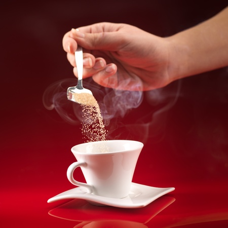 sugar: womans hand pouring brown sugar in white cup of coffee on red background