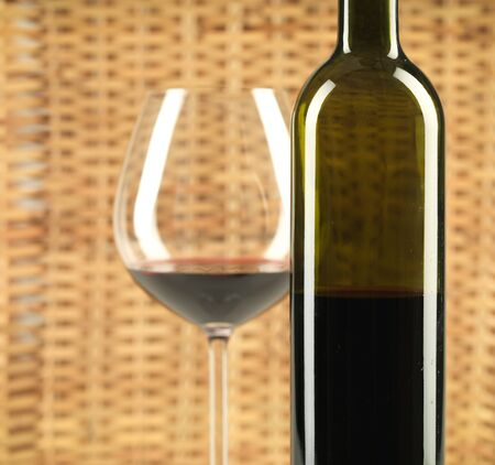 detail of bottle of wine and glass with red wine, on wicker background photo