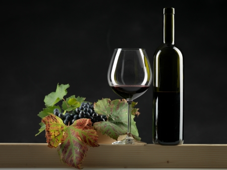 bottle of red wine, glass and bowl of grapes on black background photo