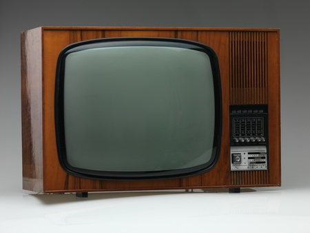 vintage black and white tv on gray background, side view photo