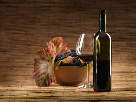 bottle of red wine, glass, grapes on wicker background photo