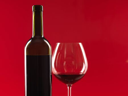 detail of bottle of wine and glass with red wine, on red background, copy space photo
