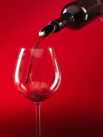 detail of red wine being poured in glass on red background photo
