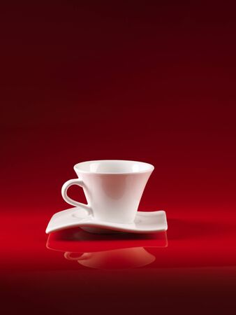 white cup and saucer of coffee, on red background photo
