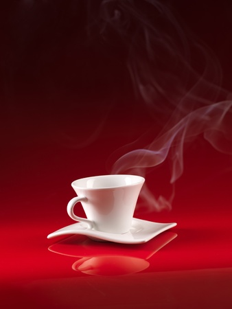 white cup and saucer with hot coffee, on red background photo