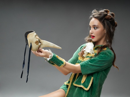 studio fashion portrait of young woman in vintage outfit, posing with venetian mask photo